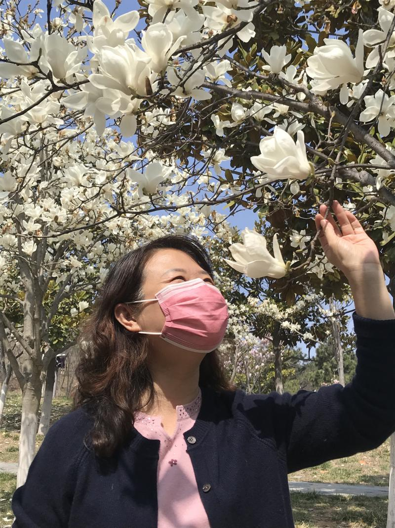 A woman appreciates spring flowers in a Qingdao city park on 3 April 2020. Photograph by Shen Hou.